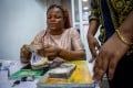 A vendor counts out Nigerian naira banknotes in Lagos, on March 29. Nigerians are contending with their highest inflation rate in four years as fears of spikes in consumer prices spread globally. Photo: Bloomberg
