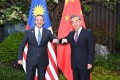 Malaysian Foreign Minister Hishammuddin Hussein (left) with his Chinese counterpart Wang Yi in Nanping, southeast China's Fujian province on Thursday. Photo: Xinhua