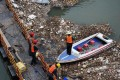 A worker clears rubbish from the Yellow River, where a survey of sewers is to be carried out to identify sources of pollution. Photo: AP