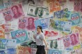 A woman walks by a money exchange shop decorated with banknotes from different countries in Hong Kong's Central district. Photo: AP