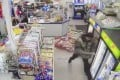 A screengrab from a video shows a man with a pole trashing a convenience store in Charlotte. Photo: Mark Sung/Grace Lee Sung via AP