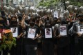 Demonstrators in Yangon on Monday hold pictures showing some of the hundreds killed during Myanmar's ongoing anti-coup protests. Photo: EPA
