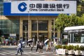 """People walk in front of a China Construction Bank branch in Shanghai. China Construction Bank """"closed and consolidated"""" 237 physical branches last year. Photo: EPA-EFE"""