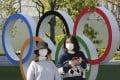People walk past the Olympic rings in Tokyo. Photo: AP