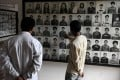 Visitors look at portraits of victims displayed at the Tuol Sleng prison. File photo: AFP