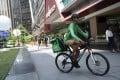 A rider for GrabFood, Grab Holdings online food-delivery platform, cycles outside Raffles Place in Singapore. The company plans to go public via a US-listed special purpose acquisiton company. Photo: Bloomberg