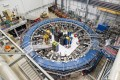 The Muon g-2 ring sits in its detector hall amids electronics racks, the muon beamline, and other equipment. The experiment studies the precession (or wobble) of muons as they travel through the magnetic field. Photo: Fermilab