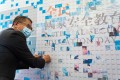 Financial Secretary Paul Chan places a personal photograph on a mural mosaic during an event marking National Security Education Day in Hong Kong on Thursday. Photo: Bloomberg