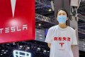 """A photo from Chinese social media went viral showing the woman at the Shanghai Auto Show 2021 standing on a Tesla sedan wearing a white T-shirt marked with Chinese characters reading """"brake malfunction"""" and a Tesla logo on Monday. Photo: Handout"""