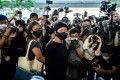RTHK producer Bao Choy surrounded by members of the press after being found guilty of improperly searching a public vehicle licence database. Photo: AFP