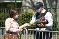A woman hands flowers to an officer on Sunday to be taken to the police station where a police official was stabbed to death on Friday in Rambouillet, near Paris. Photo: AFP