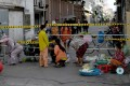 People buy vegetables next to a barricade set up in a neighbourhood due to lockdown restrictions introduced to try to halt a surge in cases of the Covid-19 coronavirus in Phnom Penh. Photo: AFP