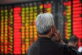 An investor looks at an electronic board showing stock information at a brokerage house in Nanjing, Jiangsu province. Photo: Reuters