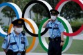 Security officers guard next to the Olympic Rings monument during an anti-Olympics rally outside the Japan Olympic Committee (JOC) headquarters near the National Stadium in Tokyo in June. Photo: Reuters