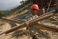 A Chinese worker carries materials for a rail line linking China to Laos. File photo: AFP