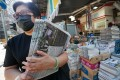 Customers snap up multiple copies of Friday's Apple Daily on the morning after five of its senior executives were arrested. Photo: Felix Wong