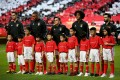 Portuguese professional football club players pose with Chinese children ahead of a game, during a brief ceremony to express solidarity with China's fight against the Covid-19 pandemic, at the Luz stadium in Lisbon on February 15, 2020. Photo: Xinhua
