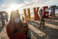 Locals and tourists attend an event organised to mark the opening of Phuket to international tourists on Patong beach. What will it take for Bali in Indonesia, which has seen day after day of record-breaking new case numbers, to reopen? Photo: Getty Images