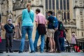 A tour guide wearing a face shield speaks to a group outside Bath Abbey in the UK, on July 5. The Delta variant is spreading, even in countries with high vaccination rates like Britain. Photo: Bloomberg
