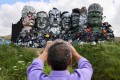 A man photographs 'Mount Recyclemore', an artwork made from electronic waste by Joe Rush and Alex Wreckage, ahead of the Group of 7 summit in Cornwall, England, on June 8. Photo: Reuters