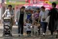 Families walk through a public park on International Children's Day in Beijing, on June 1. Photo: AP