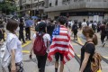 A Hong Kong demonstrator is draped in an American flag in protest against the upcoming national security legislation for the city, in Wan Chai on May 24, 2020. Photo: Bloomberg