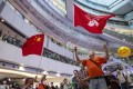 Fans gathered in a shopping mall wave the national and city flags as they watch Hong Kong swimmer Siobhan Haughey take silver in the women's 100m freestyle at the Tokyo Olympic Games on July 30. Photo: EPA-EFE