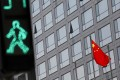 A Chinese flag flutters outside the China Securities Regulatory Commission building in Beijing. The CSRC has recently approved the applications of US firms like JPMorgan to expand their foothold in China. Photo: Reuters
