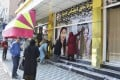 Workers at a beauty salon strip large images of women off the wall in Kabul on August 15 following news that the Taliban had swept into the Afghan capital. Photo: Kyodo