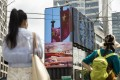 An advertising screen displays an image of Chinese flags in Shanghai on August 18. President Xi Jinping said China must pursue 'common prosperity', in which wealth is shared by all people, as a key feature of a modern economy while also curbing financial risks. Photo: Bloomberg