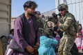 A US soldier points his gun at an Afghan man at Kabul airport on August 16 as thousands of people tried to flee Taliban rule. Photo: AFP