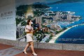 A woman walks past a property advertisement for Emerald Bay by China Evergrande in Hong Kong, on August 25. Evergrande's liquidity crisis is not an isolated case, and debt default risks remain a blight of our times. Photo: Reuters