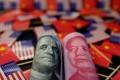 A 100 US dollar bill and a 100 yuan banknote. Photo: Reuters