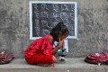 A girl with no access to internet facilities and gadgets uses a microscope as she attends an open-air class outside a house with its walls converted into blackboards as schools remained closed at a village in the Indian state of West Bengal on September 13. Photo: Reuters