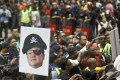 A portrait of Jho Low held aloft during a 2018 protest in Kuala Lumpur to call for his arrest over the alleged theft of billions from the Malaysian sovereign wealth fund 1MDB. Photo: AP