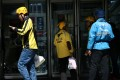 Drivers of on-demand food delivery services providers Ele.me, in blue, and Meituan Dianping, in yellow, are seen in Beijing on April 11, 2018. Photo: Reuters