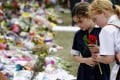 """Children offer flowers on March 21 at a memorial site in Christchurch, New Zealand, for the 50 people who died in a gun attack on two mosques last week. In his online """"manifesto"""", the alleged gunman showed support for white supremacist and anti-Muslim, anti-Jewish, anti-immigrant ideology, as well as admiration for """"non-diverse"""" nations. Photo: Kyodo"""