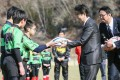Japanese Prime Minister Shinzo Abe (second right) hands an autographed rugby ball to a child at the newly built Kamaishi Recovery Memorial Stadium, one of the stadiums to be used for the Rugby World Cup. Photo Kyodo