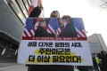 A protester holds a poster showing US President Donald Trump and North Korean leader Kim Jong-un during a rally against the United States' policy on North Korea, near the US Embassy in Seoul on Saturday. Photo: AP