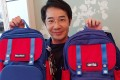 Alvin Ip Tze-fai, chief executive of Grown Up Licenses (Asia), holds the school bag designed by his company under the MoonRock brand and the one made by Anta. Photo: Enoch Yiu