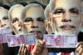 Supporters of Prime Minister Narendra Modi hold up new currency notes to support his ban on old high-denomination bills, in November 2016. Photo: EPA