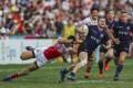 Scotland's Max McFarland tries to evade a tackle in the Bowl final against Japan. Photo: Sam Tsang