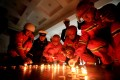 Firefighters light candles during a vigil for the colleagues they lost in a huge blaze in Sichuan province. Photo: EPA-EFE