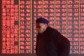 A man stands in front of an electronic board displaying stock information at a brokerage firm in Hangzhou, Zhejiang province, China April 1, 2019. Picture taken April 1, 2019. REUTERS/Stringer ATTENTION EDITORS - THIS IMAGE WAS PROVIDED BY A THIRD PARTY. CHINA OUT.
