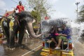A Thai mahout rides on an elephant spraying water on revellers. Photo: EPA