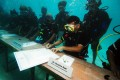 Ibrahim Didi, Minister of Fisheries and Agriculture of the Maldives signed the decree of the underwater cabinet meeting off Girifushi Island on October 17, 2009. Ministers in full scuba gear met on the seabed to draw attention to the dangers of global warming for the island nation, a tourist paradise featuring coral reefs and white sand beaches with most parts lying less than one metre (3.3 feet) above sea level. Scientists have warned it could be uninhabitable in less than 100 years. Photo: Agence France-Presse