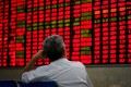 Shares traded in Shanghai have declined all but one day this week. An investor looks at an electronic board showing stock information at a brokerage house in Shanghai. Photo: Reuters