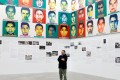 Chinese artist Ai Weiwei in front of portraits of the 43 missing Ayotzinapa College Raul Isidro Burgos students. Photo: Reuters