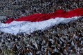 The Indonesian flag being held aloft during a campaign rally in Jakarta. Photo: EPA
