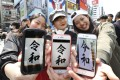"""Women show smartphone screens with the name of Japan's new era, """"Reiwa"""", in Osaka on April 1, following its announcement by the government earlier in the day. Photo: Kyodo"""